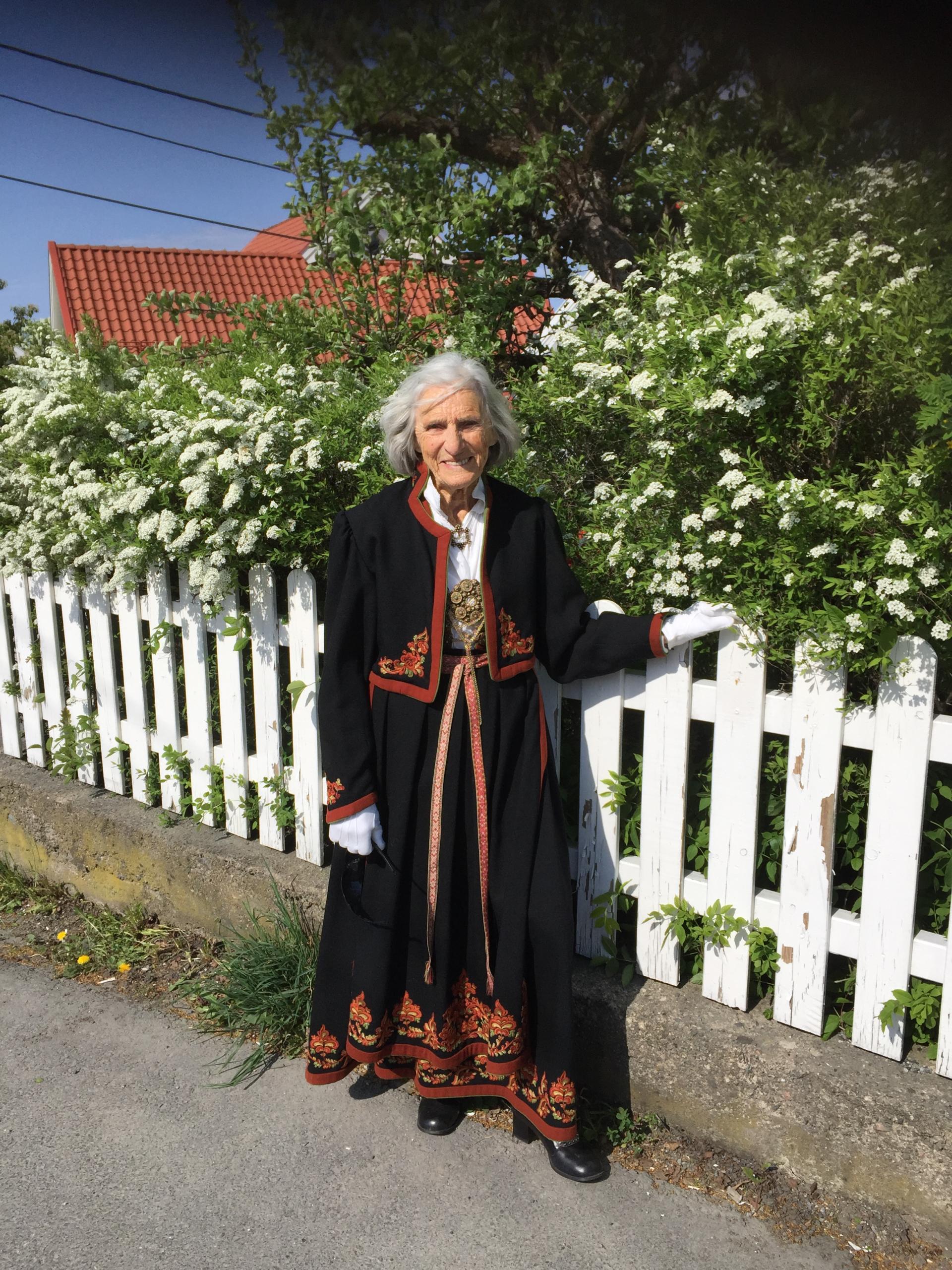 Flott dame står i bunad ved stakittgjerde en sommerdag