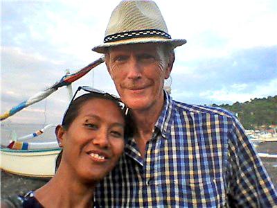 EN mann og en dame på en strand. En båt i bakgrunnen.
