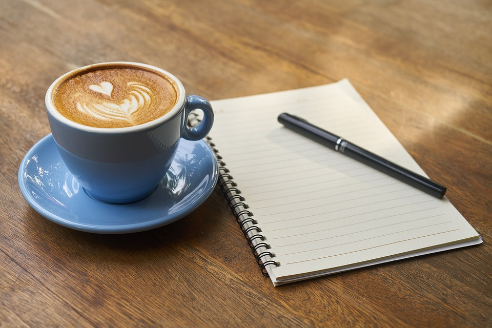 En blå kaffikopp med hjerte i. Skriveblokk og penn.