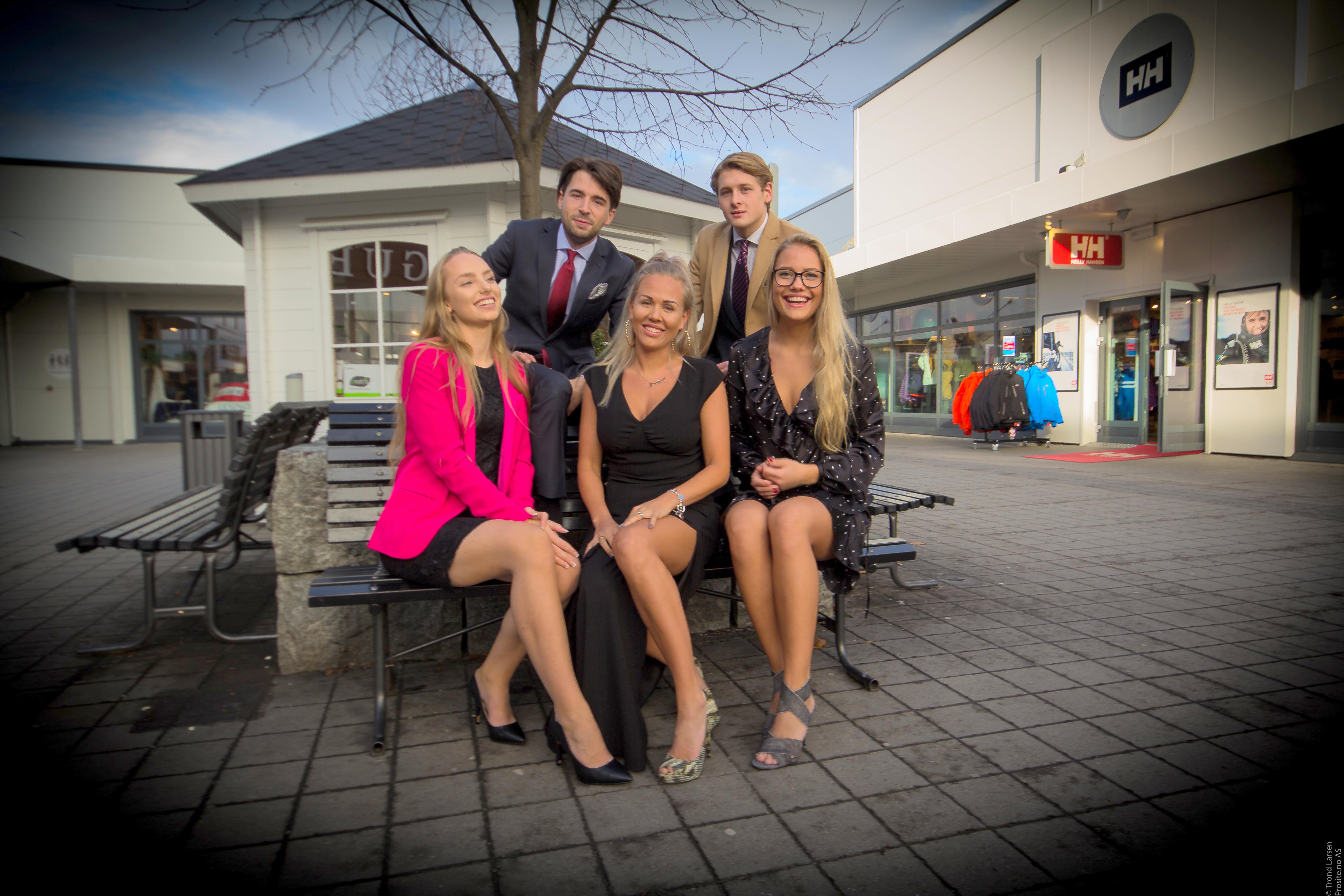 Oppstilling. Tre unge damer sitter på en benk, to unge menn står bak dem
