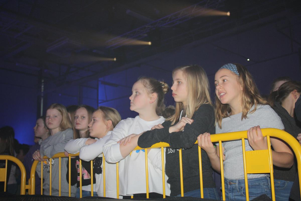 Barn bak scenesperring, ser opp på scenen