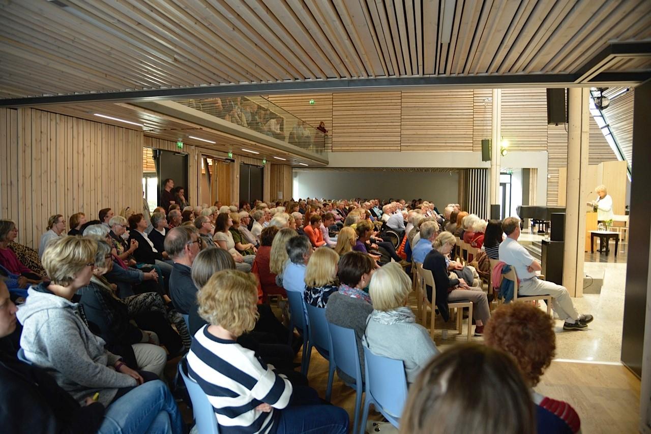 Mnge mennesker sitter i en sal hører på foredrag