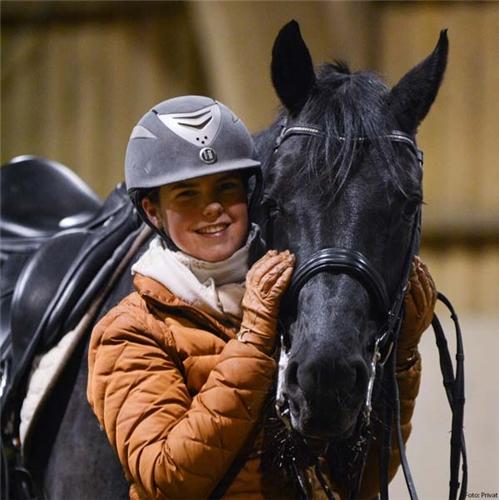 Jente poserer med hest