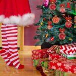 Jente står på tå, stripete strømper, juletre, presanger.