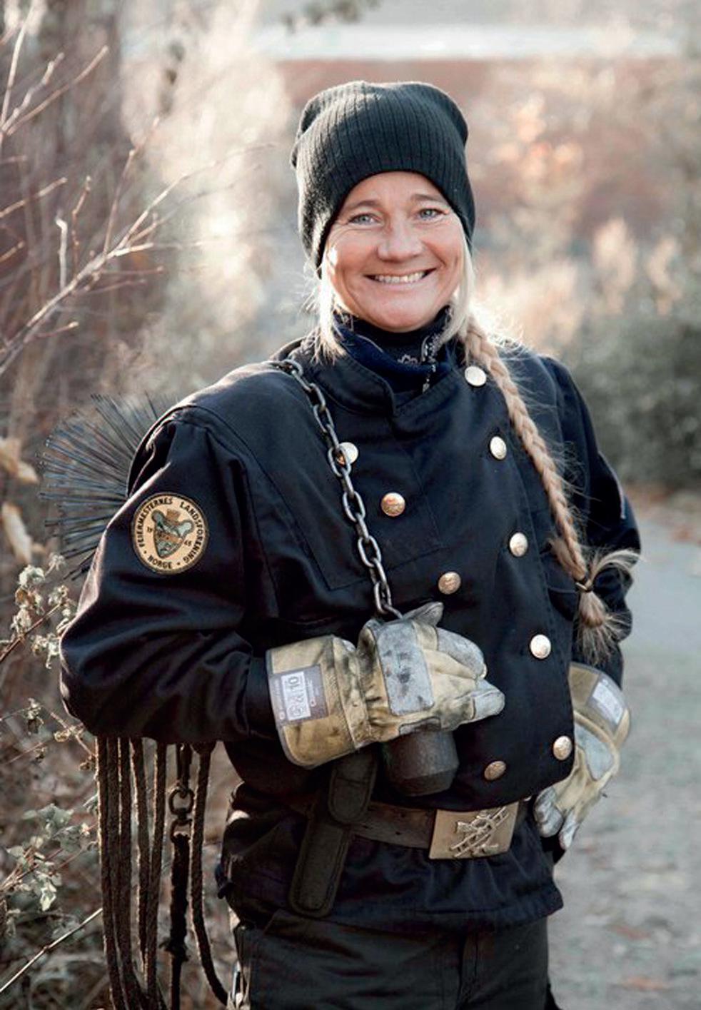 Kvinnelig feier i uniform smiler til fotografen
