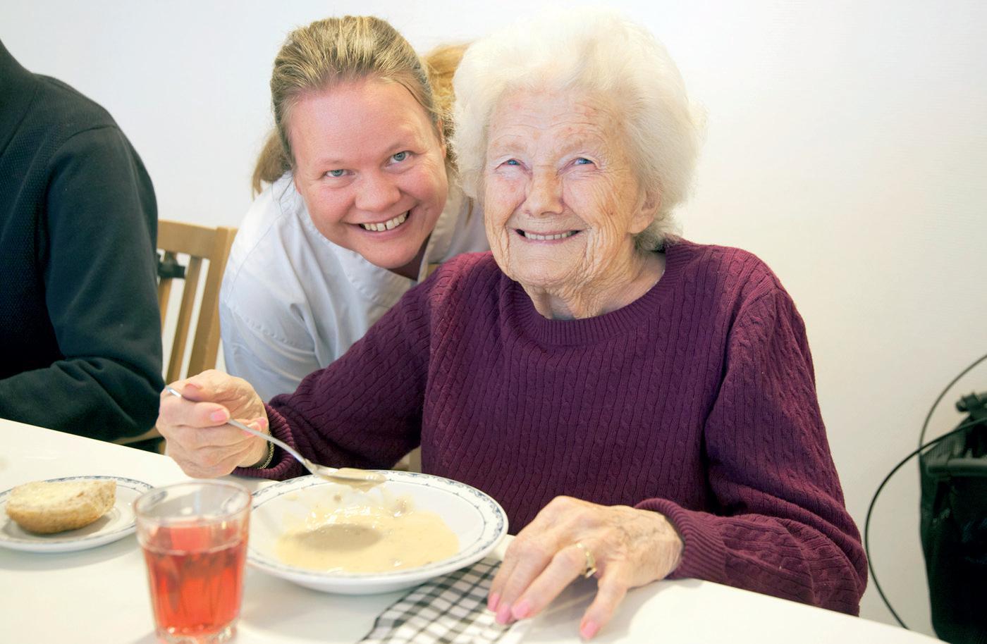 Kjøkkensjef Siw Martinsen og Ragnhild Lundmo på Vestby sykehjem. poserer. Sitter å smiler med en tallerken suppe og en skje i hånden.