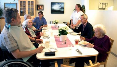 Beboerne på sykehjemmet sitter med lunsjbordet