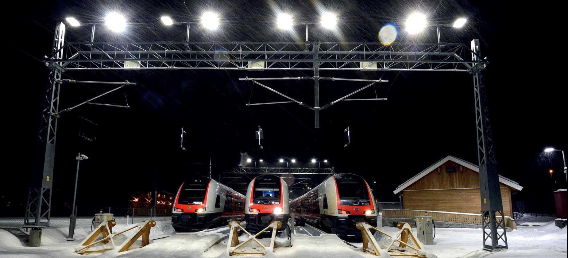 Togparkering på Eidsvold. Bilde i mørket med snø og snøvær. 3 tog vises i front med lysmast over som lyser sterkt..