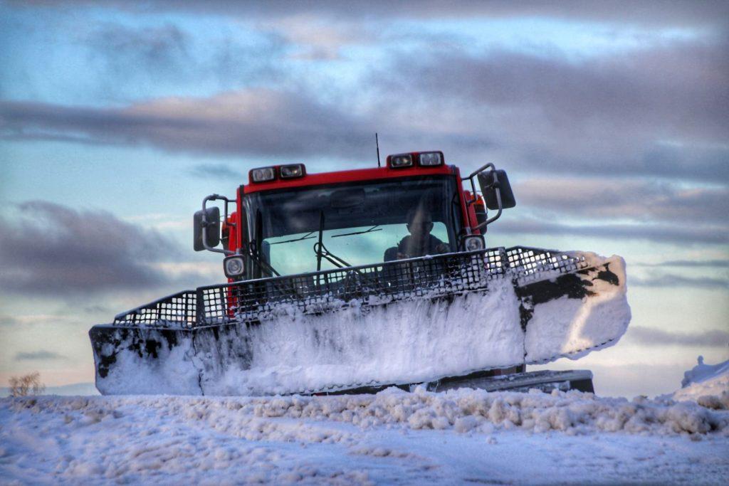 En maskin som jobber med snø i slalombakke.