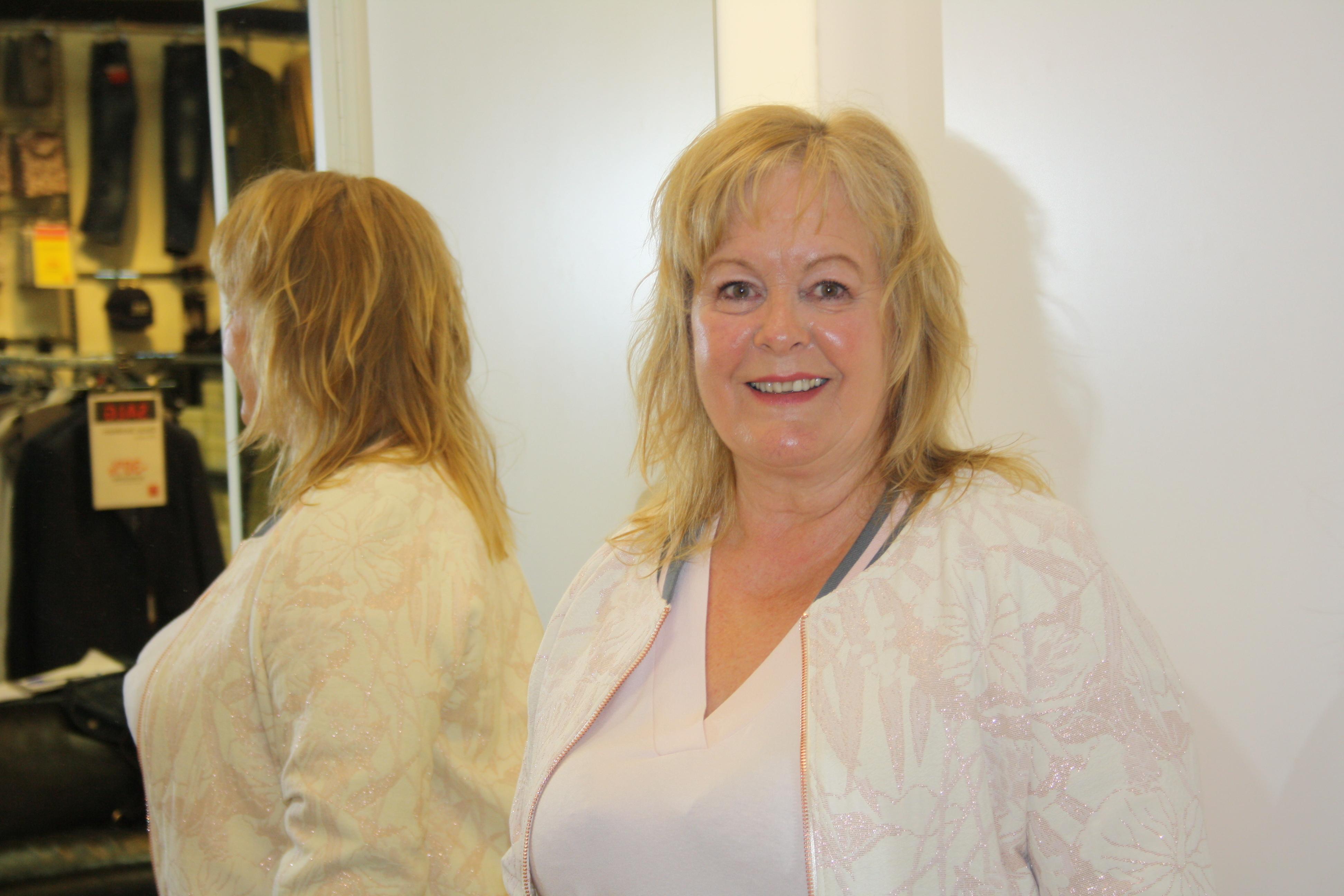 Kvinne foran speil i rosa kjole