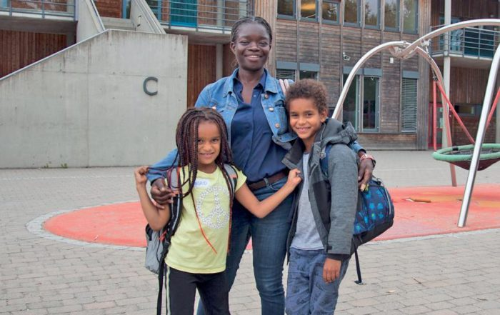 Mor og 3 barn foran skolen