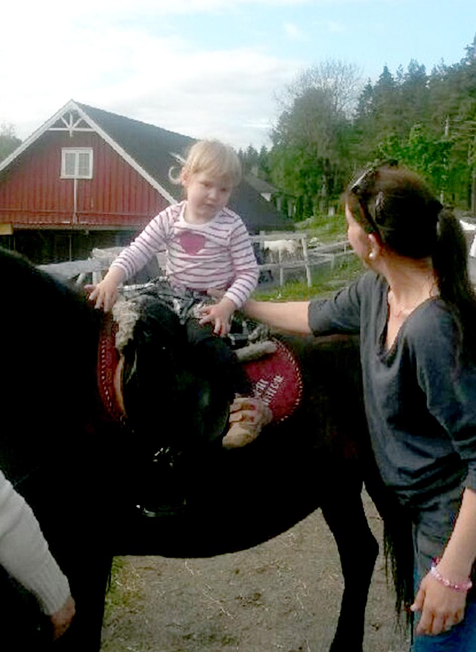 Ett lite barn på hest, en dame ved siden av, holder barnet