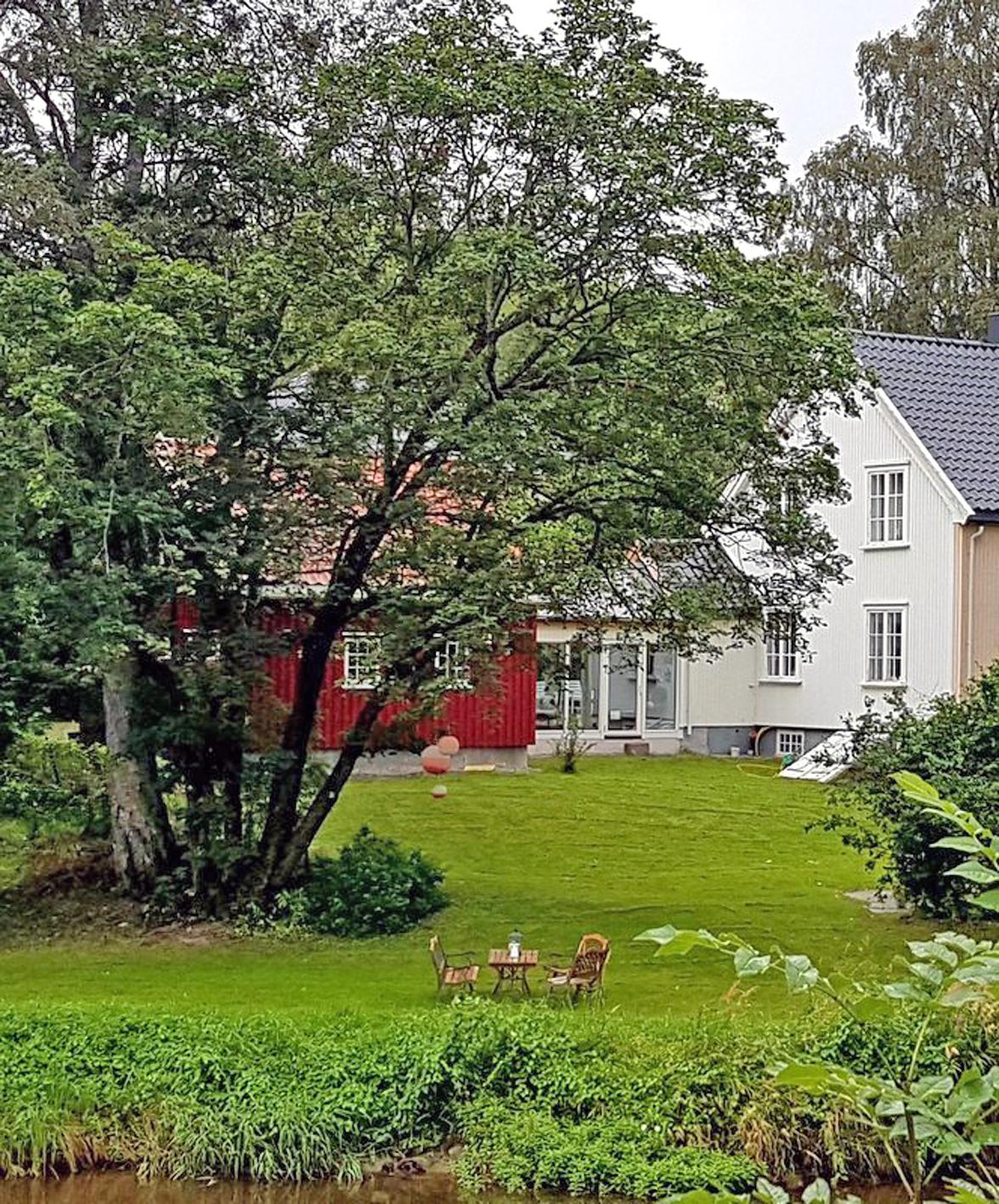 Hvitt og rødt hus og hage med tre og noen stoler og et bord ujte