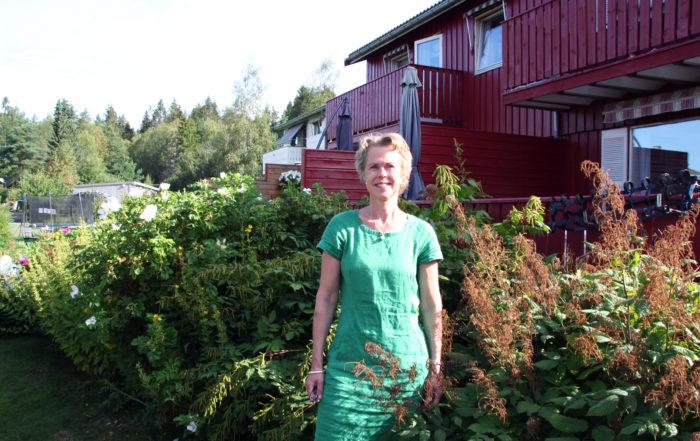 Dame (Gruppeleder SP-Tone Skretting) i hagen foran et rekkehus