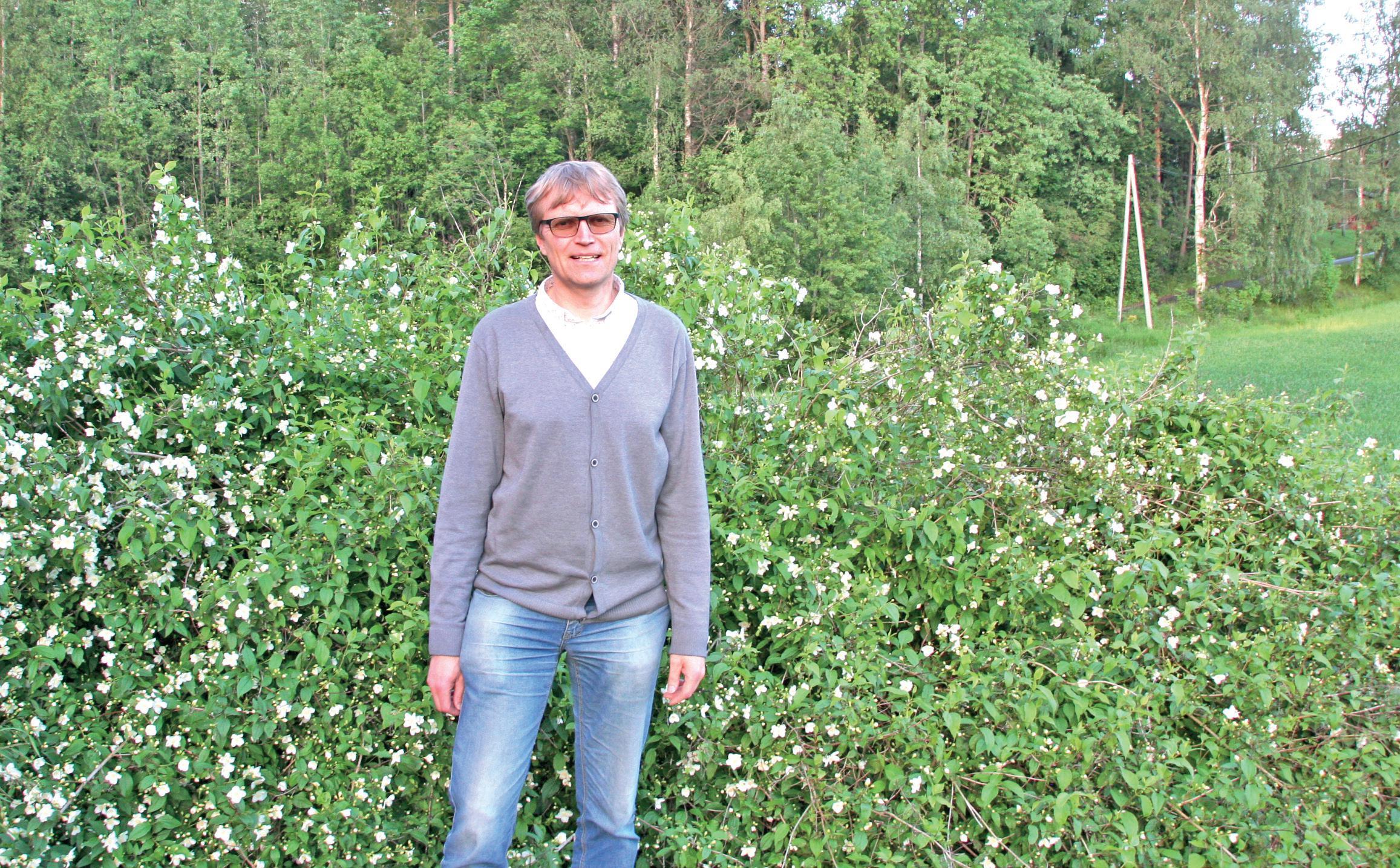 1. kandidat Lars Johan Rustad poserer foran grønn busk.
