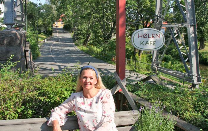 Eirin Bolle Sitter sitter på en benk på Hølen Kafe, med Hølensviadukten (Hølensbroa) i bakgrunnen.