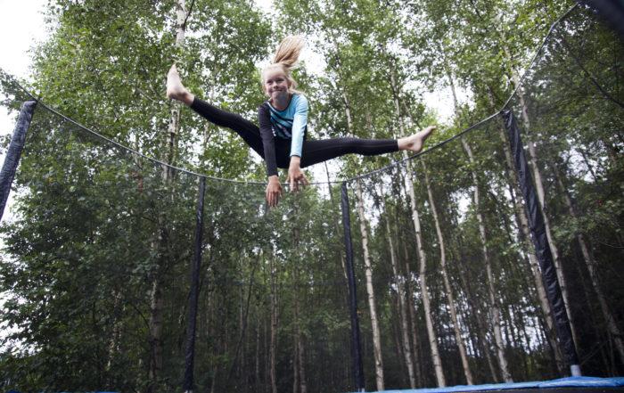 Jente som tar splitthopp på trampoline