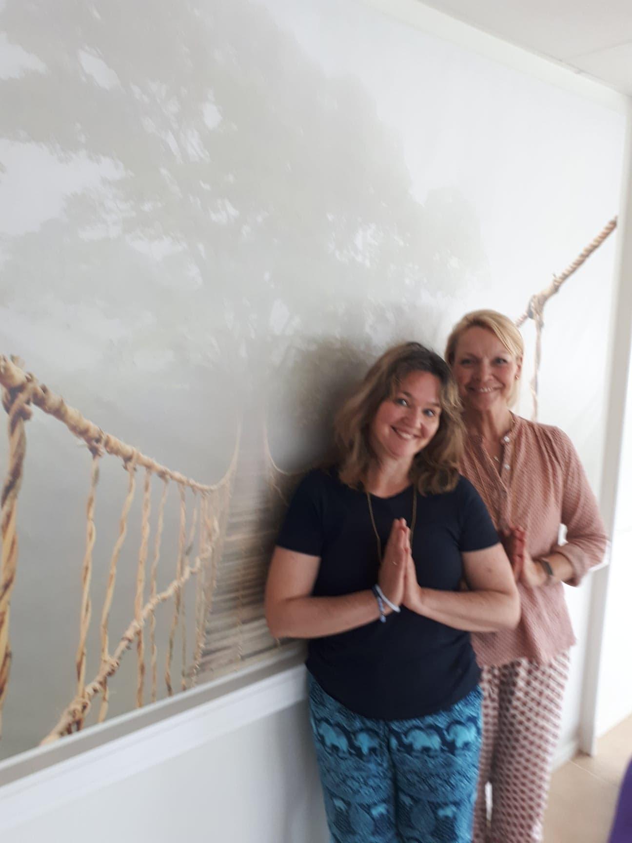 To damer står foran en vegg med et stort rolig bilde av en hengebro