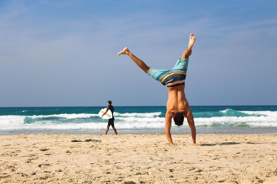 Mann står på hendene på en strand, en surfer er i bakgrunnen og det er bølger