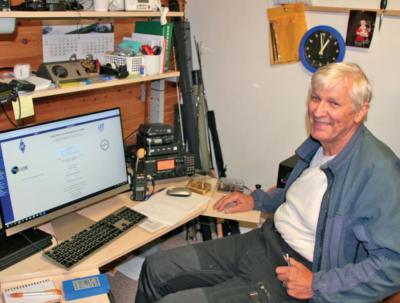 Torleif sitter med pc og radioutstyr.