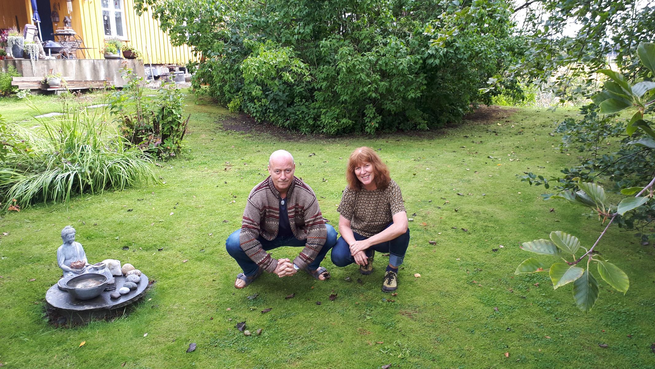 Par sitter på huk i hagen