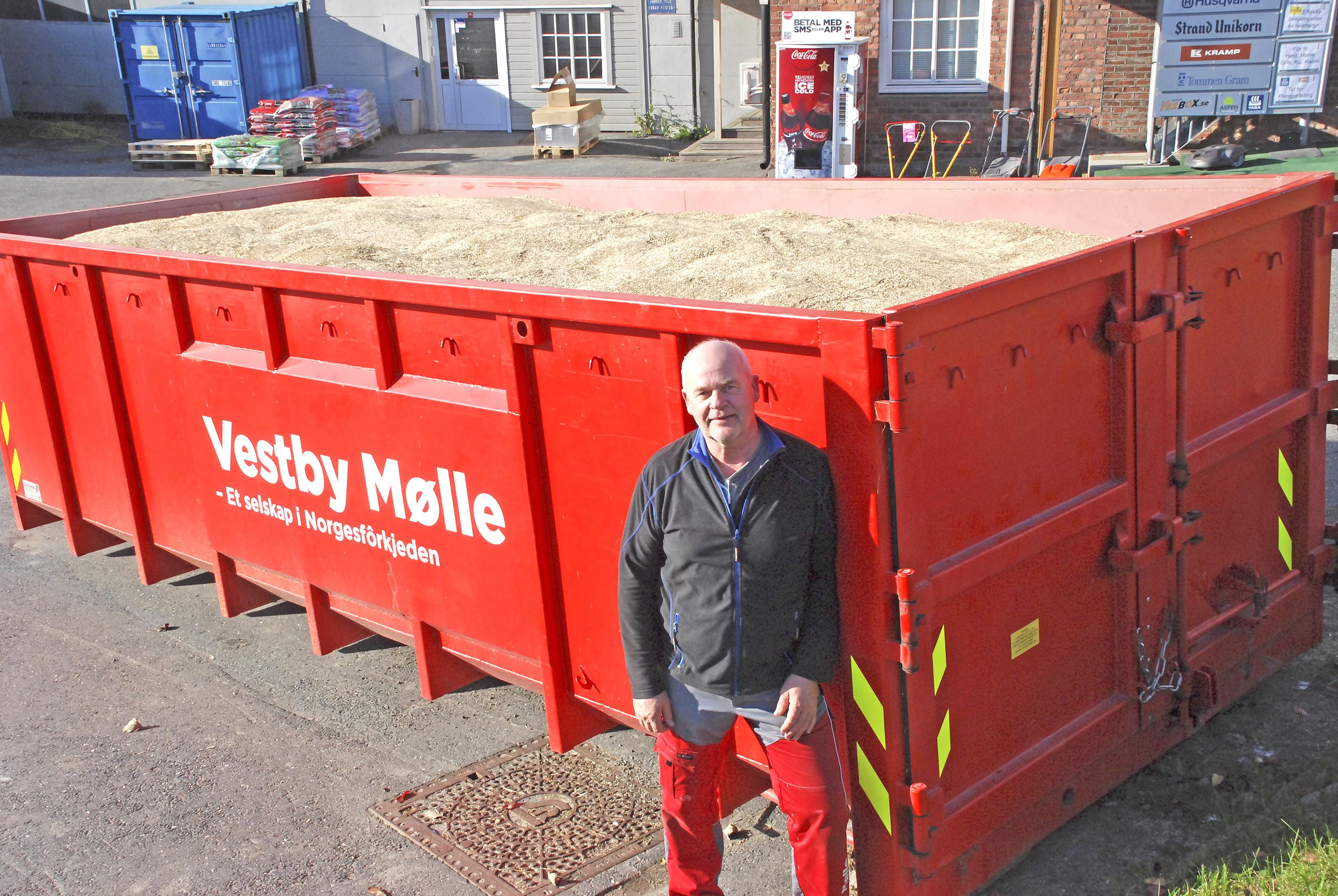 Mann står foran rød kontainer med korn. Det står Vestby Mølle på kontaineren.
