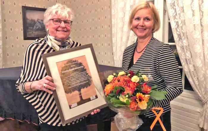 To damer holder en pris i ramme og blomster