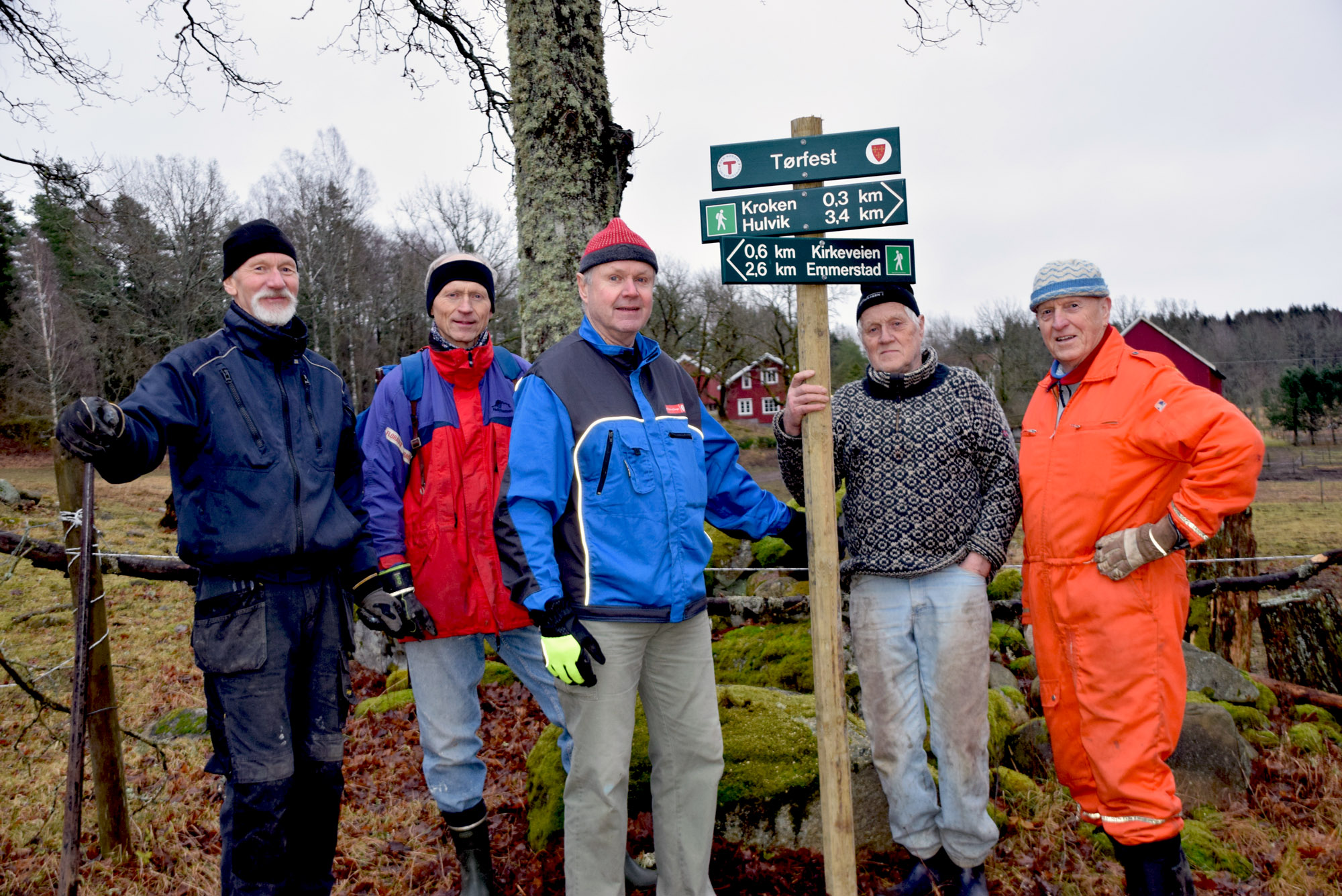 5 menn står ved et skilt i skogen