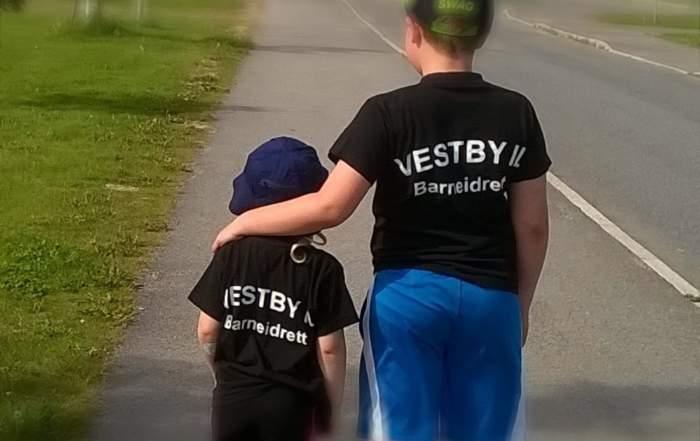 """To barn står sammen, den eldre holder rundt den yngre. Det står """"barneidretten"""" på ryggen deres."""