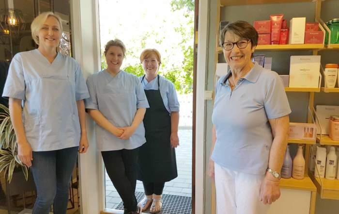 Fire damer står i døråpningen og smiler