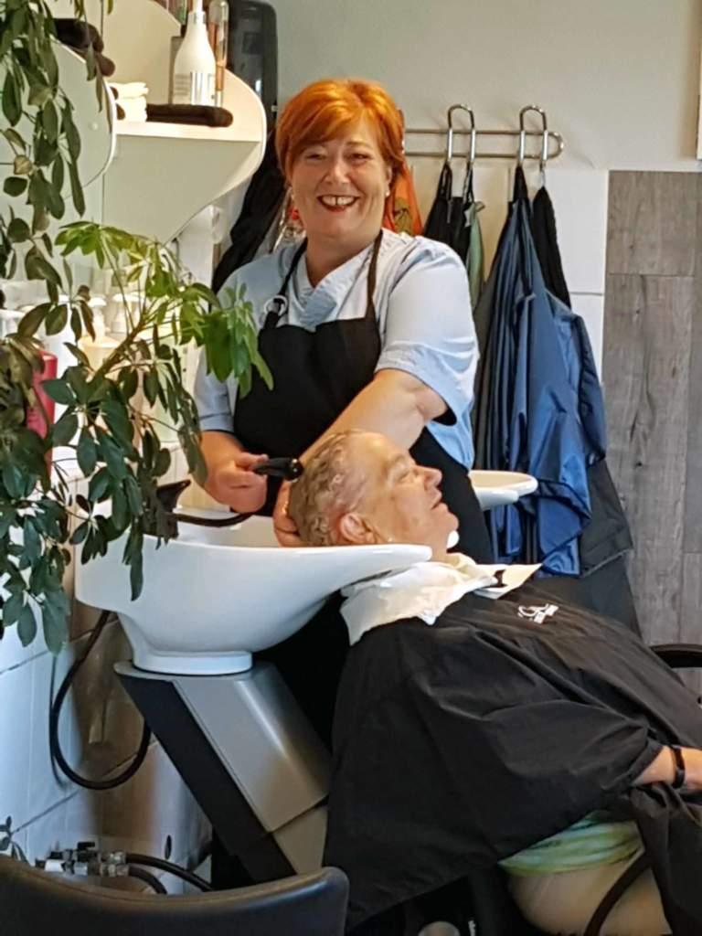 Frisørdame vasker håret til kunde