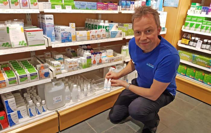 mann sitter på huk viser varer på apotek