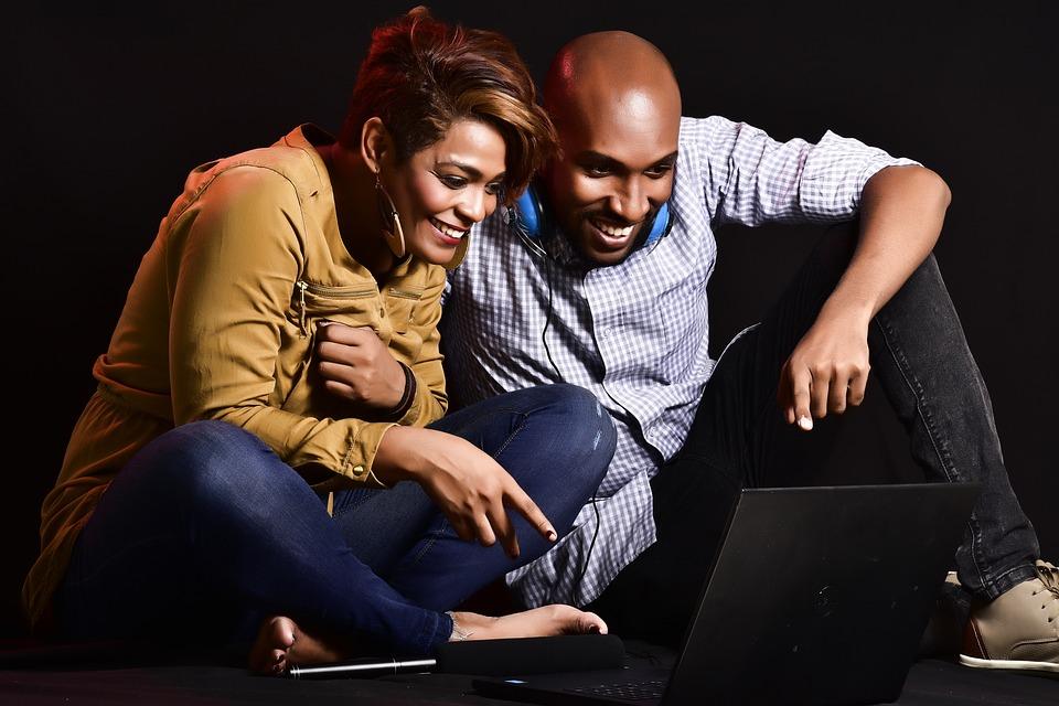 to personer ler og ser på en laptop: