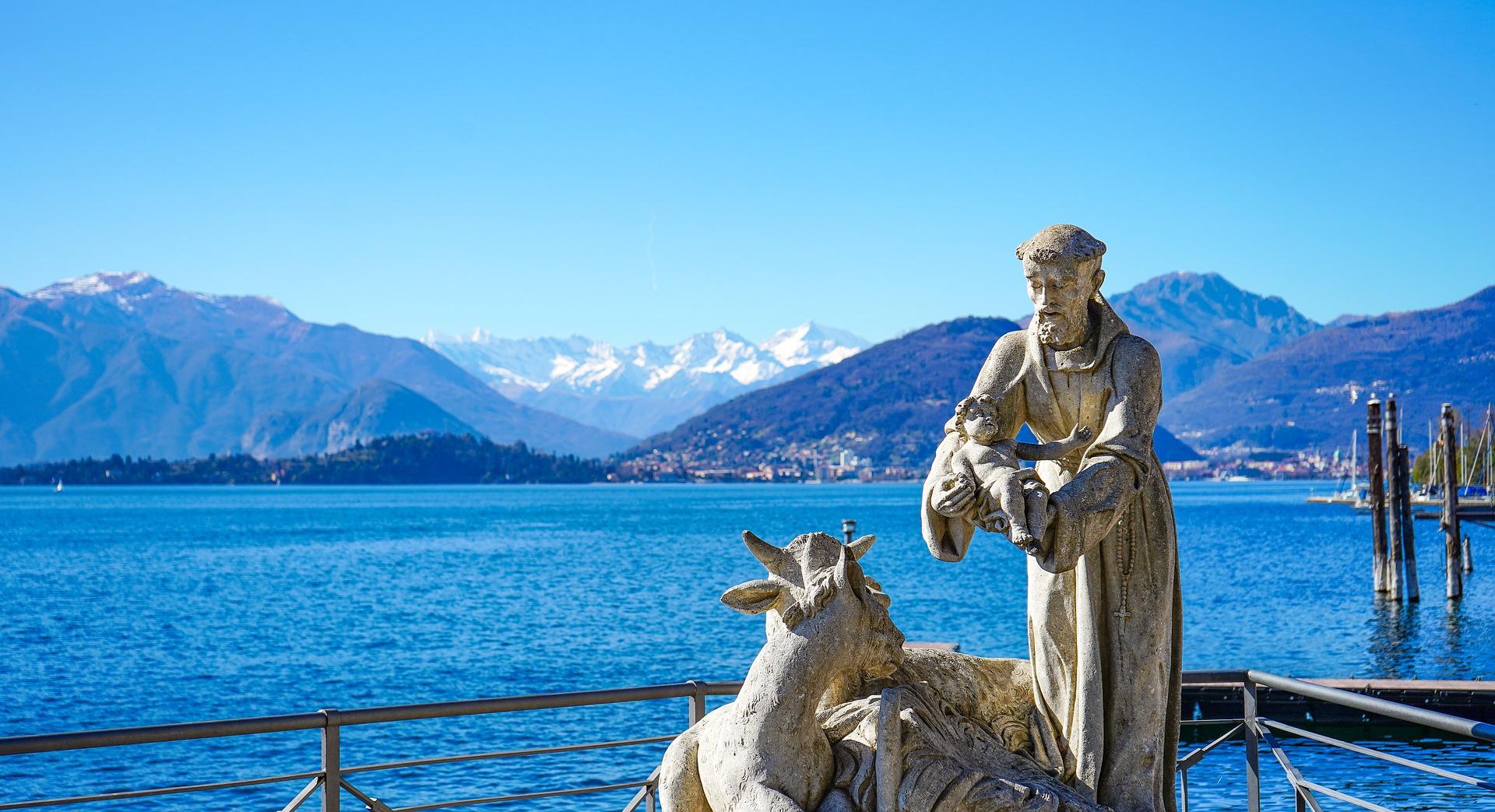Statue Frans av Assisi med julekrybbe holder jesus barnet.