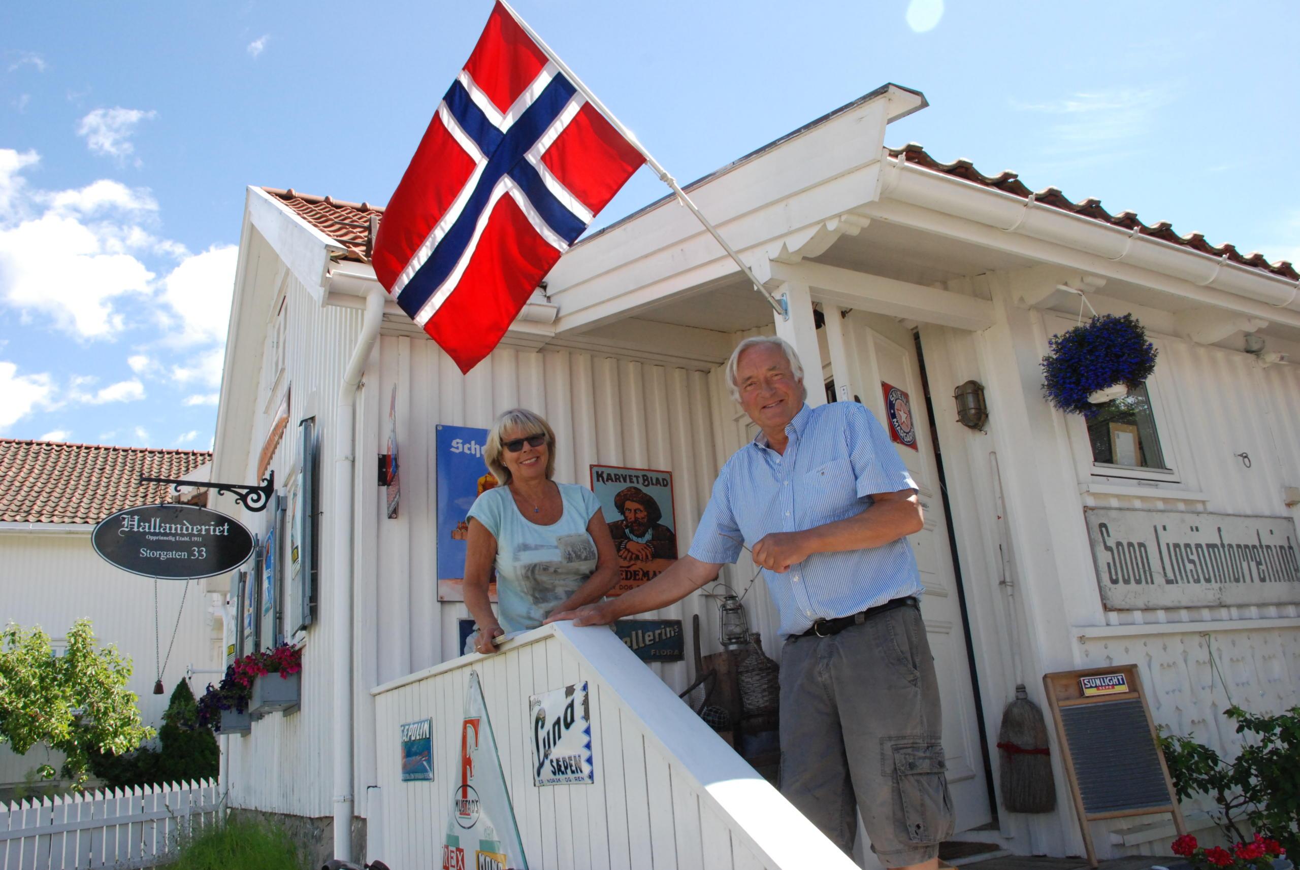 Knut og Gro Hallan utenfor hallanderiet nbak dem ettflagg