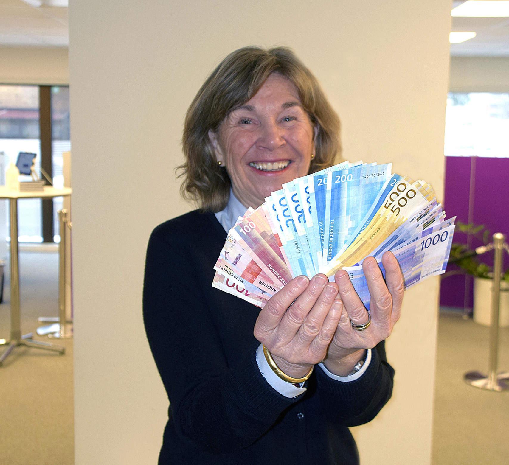 Kari viser 10 000 kroner i en vifte som en kortstokk.
