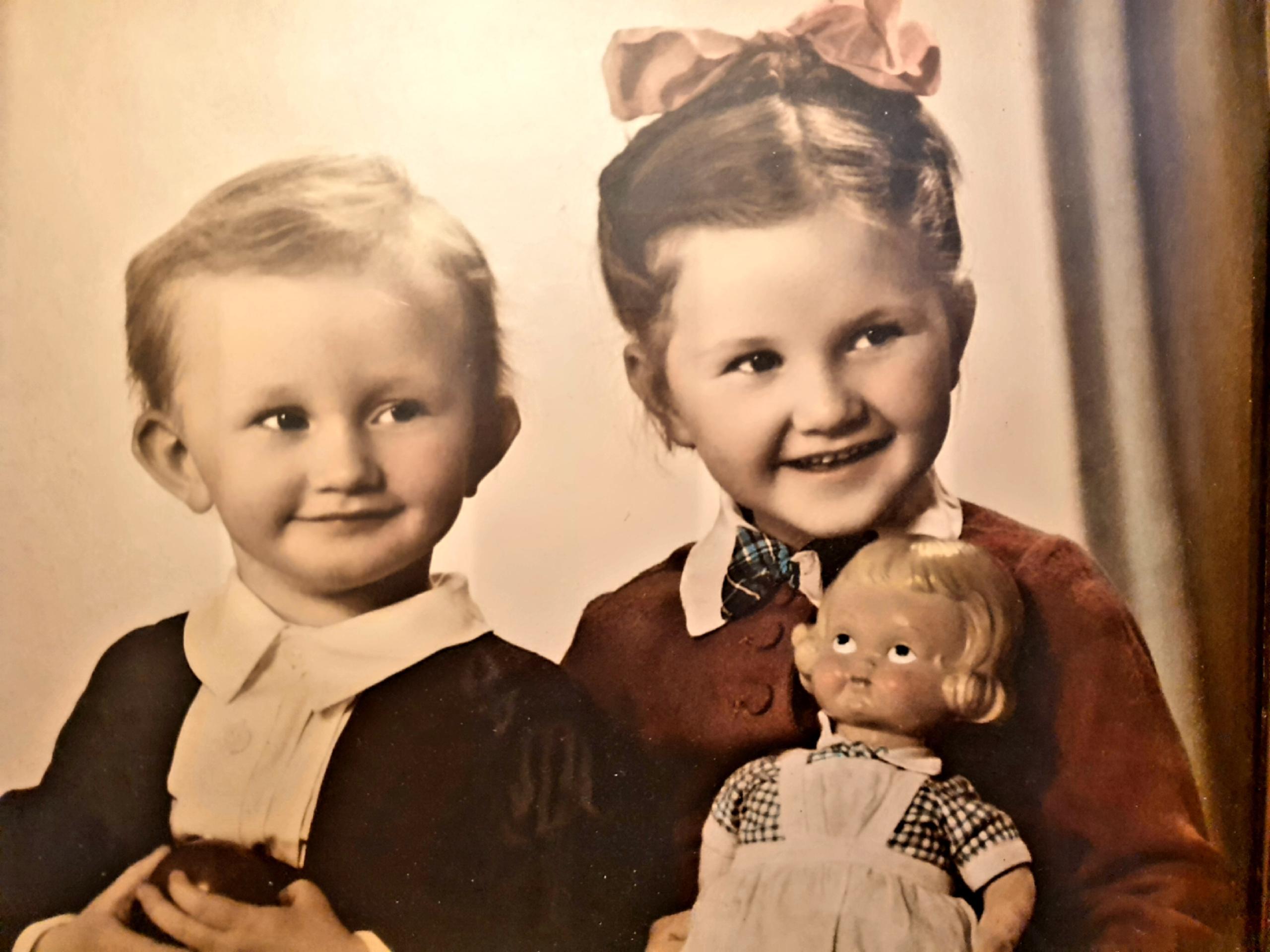 Gammelt bilde av to barn. Jenta holder en sykepleierdokke.