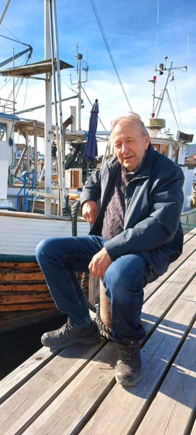 mann sitter ved fiskebåt