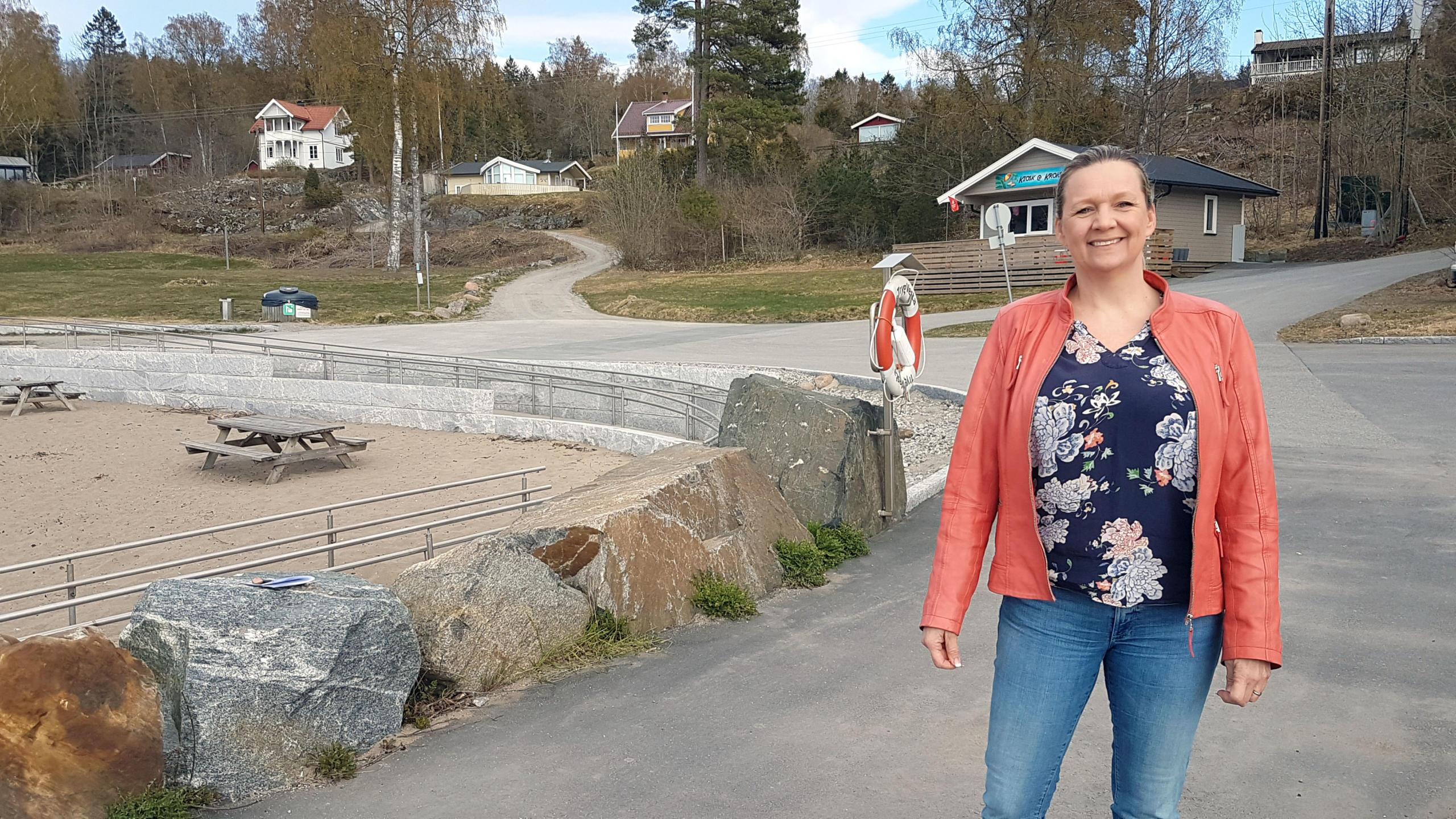 Smilende dame med oransje jakke med kiosken på Krokstrand i bakgrunnen