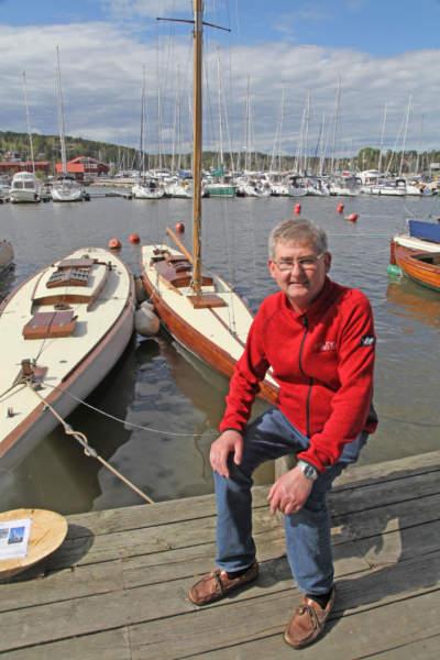 mann ved båthavna m/ seilbåter